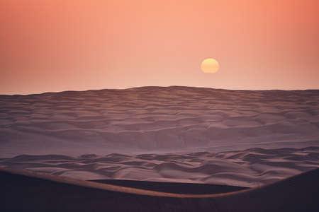Sand dunes in desert landscape at sunrise. Wahiba Sands, Sultanate of Oman.