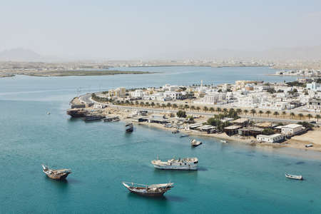 Bay with traditional wooden Dhow ships. Coastline of old city Sur in Sultanate of Oman. Stock Photo