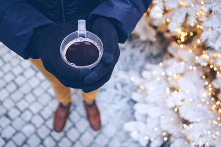 Man holding cup of mulled wine against illuminated christmas tree.  Munich, Germany.