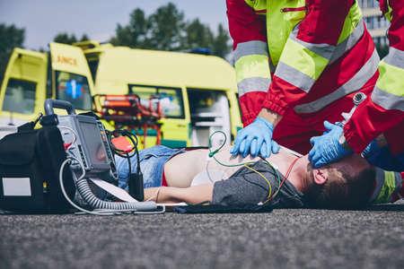 Reanimación cardiopulmonar. Equipo de rescate (médico y paramédico) resucitando al hombre en la vía. Foto de archivo