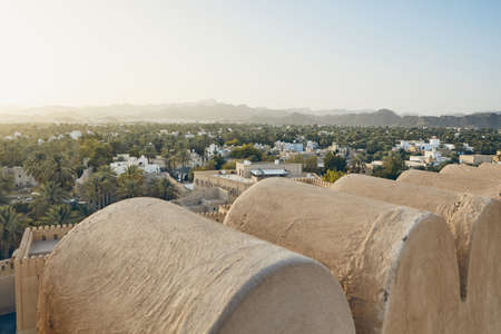 City against mountain range at idyllic sunset. Nizwa in Sultanate of Oman.