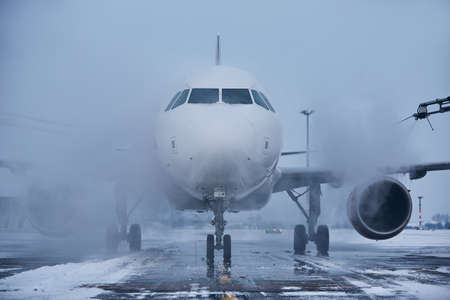 Winter day at the airport. Deicing of airplane before flight.