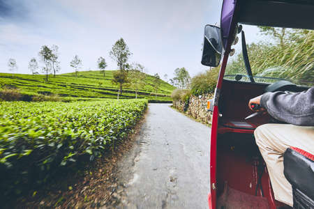 Tuk tuk taxi on the road through tea plantations in Sri Lanka.