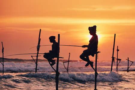 Silhouettes des pêcheurs traditionnels. Pêche traditionnelle sur échasses près de Galle au Sri Lanka.