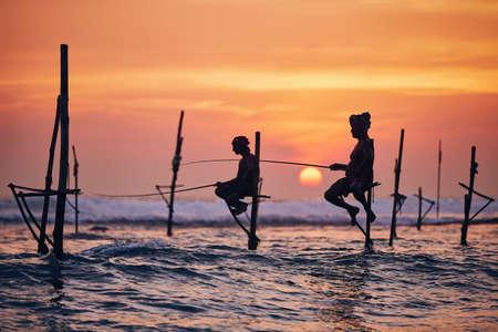 Silhouettes of the traditional fishermen. Traditional stilt fishing near Galle in Sri Lanka.