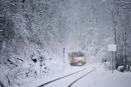 Railway in winter. Passenger train leaving from railroad station coverd by snow. 스톡 콘텐츠
