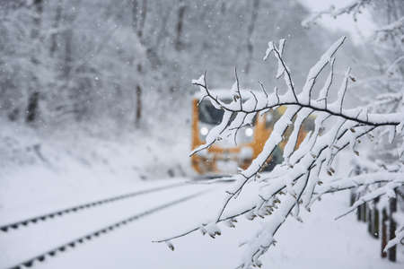 Railway in winter. Passenger train commuting to railroad station coverd by snow. Фото со стока