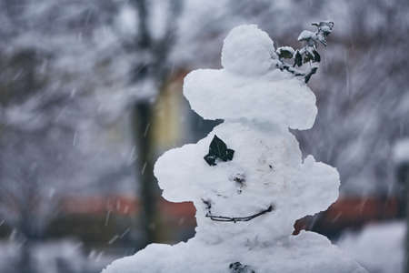 Winter in the city. Head of big snowman during snowfall. Imagens - 117267163