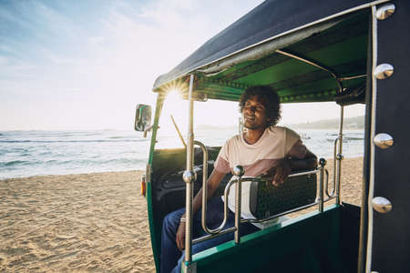 Young tuk tuk driver waiting for passenger against sand beach and sea in Sri Lanka. Stock Photo