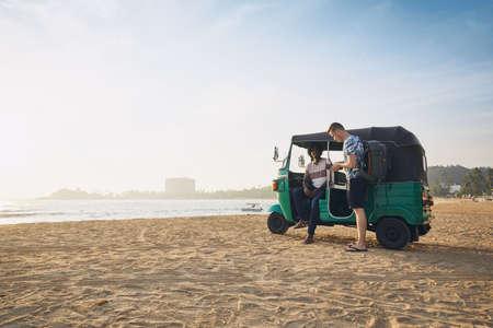 Tuk tuk driver with passenger against sand beach and sea in Sri Lanka. Stock Photo