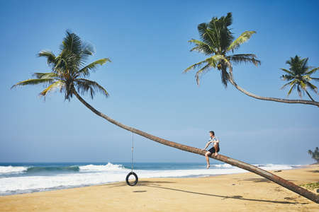 Young man sitting on the palm tree. Relaxation on the sand beach. Sri lanka Stok Fotoğraf