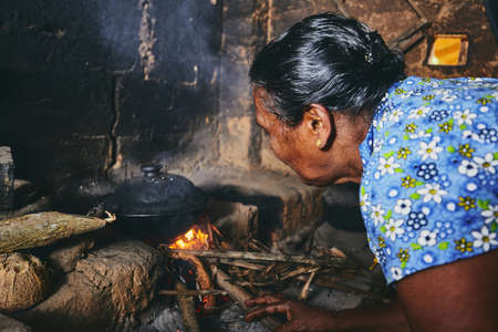 Rural woman preparing food in traditional home kitchen. Domestic life in Sri Lanka.