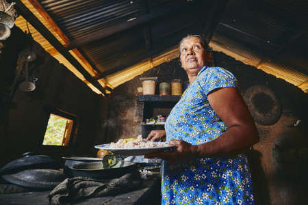 Rural woman preparing food in traditional home kitchen. Domestic life in Sri Lanka. Stock Photo