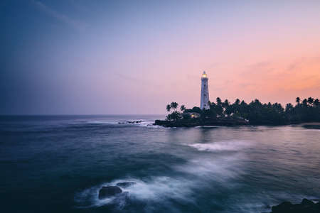 Illuminated lighthouse in the middle of palm trees. South coast of Sri Lanka at sunset. Фото со стока - 117267372