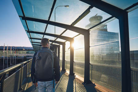 Young man with backpack walking to airport terminal at sunset. Stock Photo