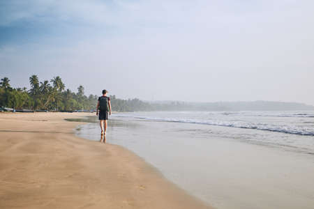 Young tourist walking on the sand beach against palm trees. Coastline near Tangalle in Sri Lanka.
