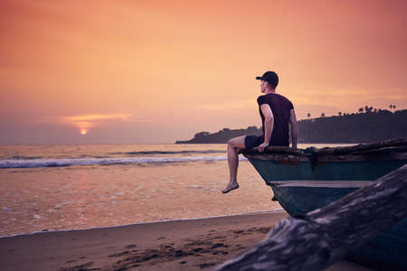 Young man sitting on fishing boat at sunrise. Contemplation on idyllic sand beach near Tangalle in Sri Lanka.