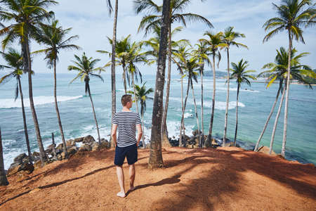 Young man with walking between palm trees against sea. Coastline in Sri Lanka.