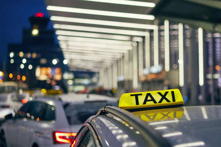 Lighting taxi sign on the roof of car against airport terminal at night. Stock Photo