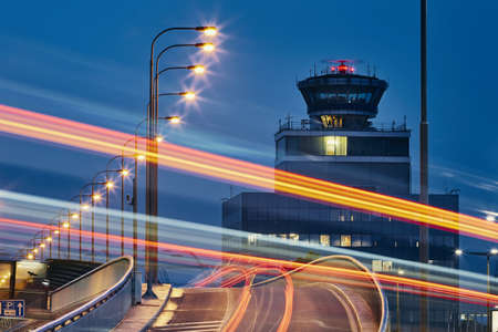 Light trails of the cars on the road to airport against air traffic control tower.