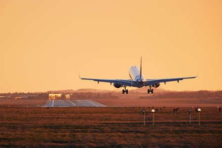 Traffic at airport. Airplane landing on runway at sunset. Stock Photo