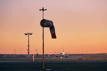 Striped windsock against taxiing airplane. Airport at sunset.