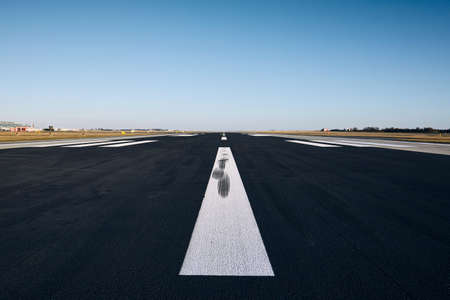 Surface level of airport runway with road marking against clear sky. Stock Photo