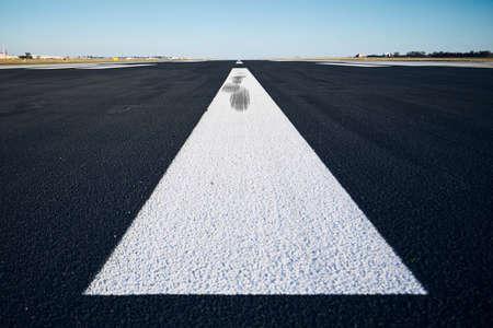 Nivel de la superficie de la pista del aeropuerto con señalización vial contra el cielo despejado.