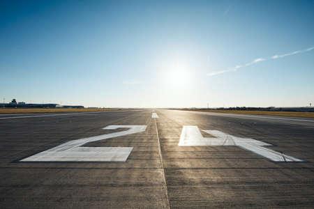 Oberflächenniveau der Landebahn des Flughafens mit Straßenmarkierung und Nummer 24 gegen klaren Himmel. Standard-Bild