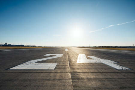 Surface level of airport runway with road marking and number 24 against clear sky. 스톡 콘텐츠 - 119803494