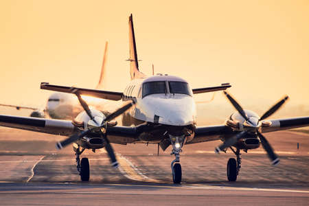 Modern propeller plane against commercial airplane on runway. Traffic at airport during sunset. Stock fotó - 120139456