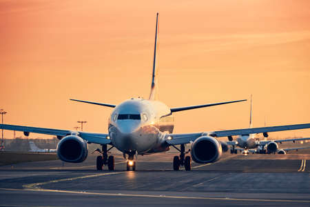 Flugzeuge in Reihe Rollen zur Startbahn für den Start. Verkehr am belebten Flughafen bei Sonnenuntergang. Standard-Bild
