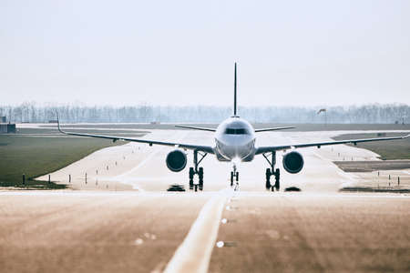 Traffic at airport. Front view of airplane on taxiway after landing.