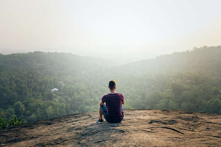 Young man resting on top of rock. Landscape at foggy sunset in Sri Lanka.