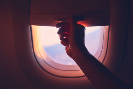 Travel by airplane. Hand pulling down or up window blinds during flight. Banco de Imagens