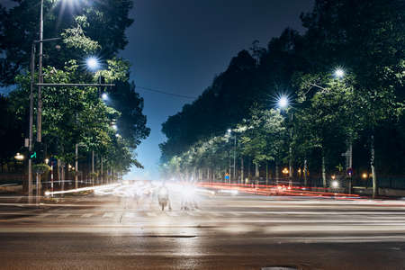 Motorcycles waiting on crossroad. Light trails of traffic in city. Hanoi at night, Vietnam. Stock Photo