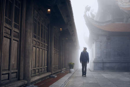 Traveler walking in mysterious fog to Buddhist temple on peak Fansipan - highest mountain in Indochina, Vietnam. Stock Photo