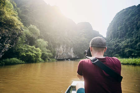 Photographer with camera on boat. Young man taking photo of river against karst formation near Tam Coc in Ninh Binh province, Vietnam.