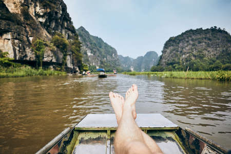Legs of man on boat against karst formation near Tam Coc in Ninh Binh province, Vietnam. Themes travel, relaxation and vacations.