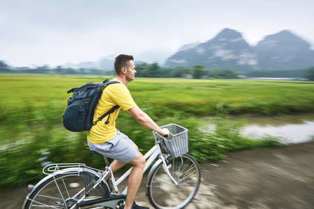 Trip by bike. Man with backpack bicycling on road against karst formation in Ninh Binh province, Vietnam. Stock Photo