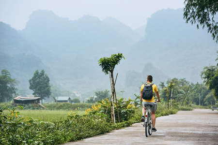 Trip by bike. Man with backpack bicycling on road against karst formation in Ninh Binh province, Vietnam. Imagens