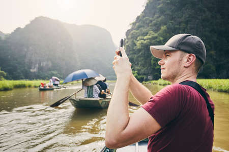 Tourist with mobile phone on boat. Young man photographing of river against karst formation near Tam Coc in Ninh Binh province, Vietnam.