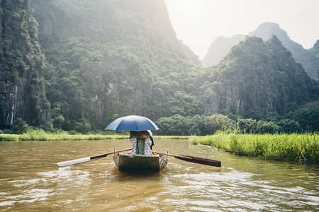 Boat with tourists against karst formation near Tam Coc in Ninh Binh province, Vietnam. Themes travel, relaxation and vacations.