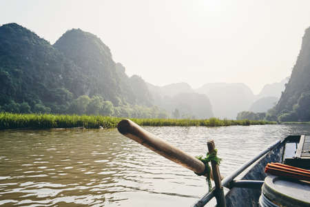 Rowboat against karst formation near Tam Coc in Ninh Binh province, Vietnam. Themes travel, relaxation and vacations.