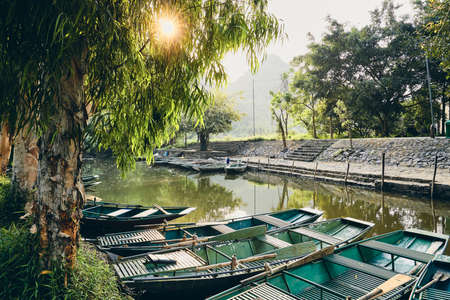 Waterfront with rowboats against karst formation at sunset. Ninh Binh province, Vietnam.