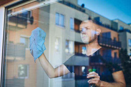 Man cleaning window with rag and cleanser spray at home. Themes housework and housekeeping. 스톡 콘텐츠
