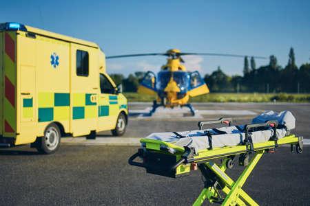 Bahre gegen Krankenwagen und Hubschrauber des Rettungsdienstes. Themen Rettung, Hilfe und Hoffnung.