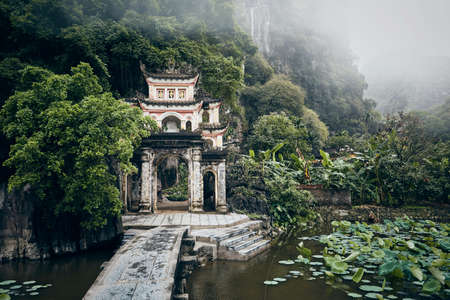 Scenery with old temple against karst formation in fog. Stone bridge over lake leading to Bich Dong Pagoda. Popular tourist destination in Ninh Binh province, Vietnam Reklamní fotografie