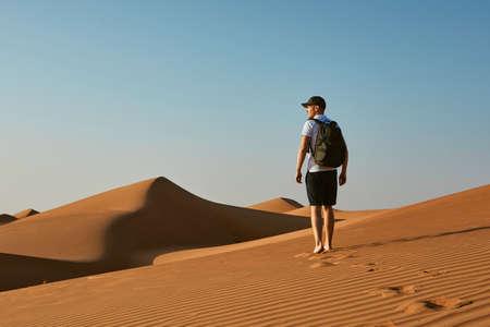 Young tourist in desert. Man with backpack walking on sand dune. Desert Wahiba Sands in Oman. Banco de Imagens