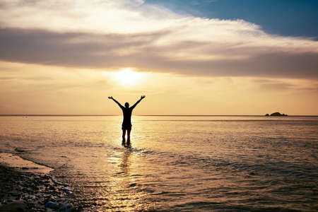 Rear view of happy man with arms outstretched standing in sea at amazing sunset. Banco de Imagens